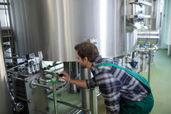 Worker checking machinery. At brewery Stock Photos