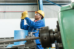 Worker checking quality behind an industrial machine. Asian worker checking quality behind an industrial machine indoors in the factory Royalty Free Stock Photo