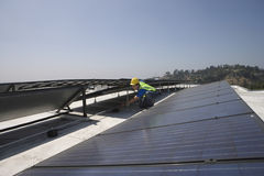 Worker Checking Solar Panels On Rooftop Royalty Free Stock Image
