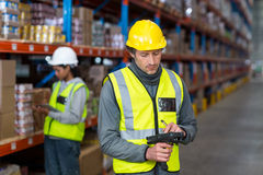 Worker checking stock with digital equipment. In warehouse Royalty Free Stock Images