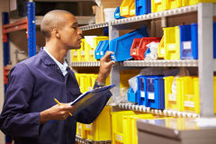 Worker Checking Stock Levels In Store Room. Looking In Blue Box Whilst Holding A Clipboard And Pen Royalty Free Stock Photos