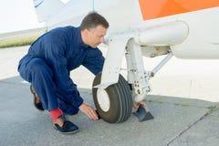 Worker checking undercarriage plane. Worker checking undercarriage of plane Royalty Free Stock Photo