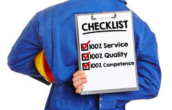 Worker with checklist for quality. And service on a clipboard Royalty Free Stock Photos