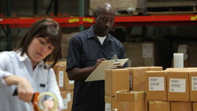 Worker Checks Clipboard As Colleague Seals Boxes stock video