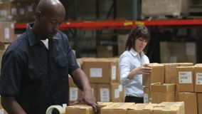 Worker Checks Clipboard As Colleague Seals Boxes. Male factory worker sealing packages for dispatch as female colleague checks boxes against clipboard. Shot on stock footage