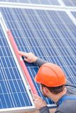 Worker checks the joint is verified by the horizontal marker of solar panels. Employee in blue uniform and an orange helmet checks the joints verifies the Stock Images