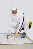 Worker checks old tiles base with hammer Royalty Free Stock Image