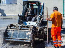 Worker checks the progress of the Milling of asphalt. For road reconstruction accessory for skid steer Royalty Free Stock Photos