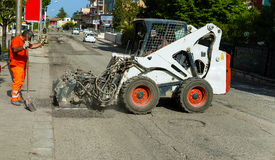 Worker checks the progress of the Milling of asphalt. For road reconstruction accessory for skid steer Stock Photos