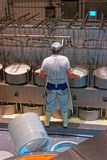 Worker of the cheese-making factory is busy putting the pressure Royalty Free Stock Photos