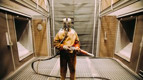 Worker in chemical rubber suit and respirator in chemical processing plant