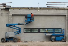 A worker on a cherry picker finishes the newly constructed facade of a new building. On the right an aerial platform.  stock photos