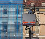 A worker on a cherry picker, repairs a lamp post of public lighting in a city street . A technician on a cherry picker, repairs a lamp post of public lighting royalty free stock image
