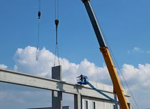 Worker on a cherry picker, together with telescopic crane, installs a concrete block wall. Worker on a cherry picker, together with telescopic crane, installs a royalty free stock photography