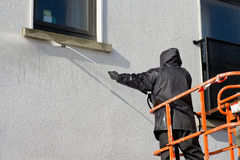 Worker in cherry-piker. Washing A building exterior Stock Image