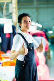 Worker in a chinese garment factory. Worker or production manager standing proudly in a Chinese textile factory, it is his workplace Stock Image