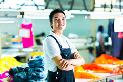 Worker in a chinese garment factory. Worker or production manager standing proudly in a Chinese textile factory, it is his workplace Stock Photo