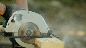 Worker with a circular saw. Is sawing a board many sawdust, slow motion stock video footage