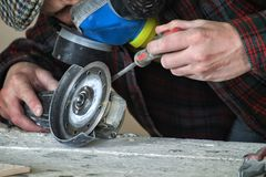 Master clamps protective casing in an angle grinder. Worker clamps protective casing in an angle grinder royalty free stock image
