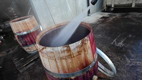 Worker clean barrel at high pressure in vine cellar