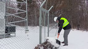 Worker clean snow near gates stock video footage