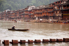 Worker clean up the river in Fenghuang ancient city. Royalty Free Stock Photos