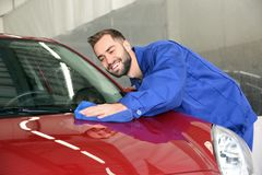 Worker cleaning automobile bonnet at car wash royalty free stock image