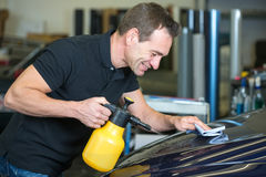 Worker cleaning car with cloth and spray bottle. In garage or workshop Stock Photo