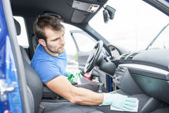 Worker cleaning car. Man cleaning vehicle with sponge Royalty Free Stock Images