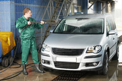 Worker cleaning car with pressured water. Manual car washing cleaning with foam and pressured water at service station Royalty Free Stock Photos