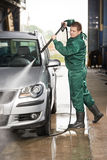Worker cleaning car with pressured water. Manual car washing cleaning with foam and pressured water at service station stock photo