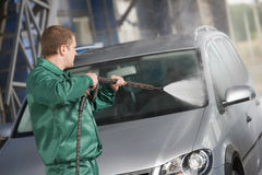 Worker cleaning car with pressured water. Manual car washing cleaning with foam and pressured water at service station stock images