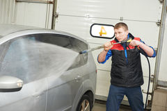 Worker cleaning car with pressured water. Manual car washing cleaning with foam and pressured water at service station royalty free stock photography