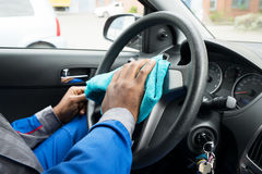 Worker Cleaning Car Steering Wheel. Close-up Of A Male Worker Cleaning Car Steering Wheel With Cloth Royalty Free Stock Photography
