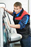 Worker cleaning car with water and sponge Royalty Free Stock Photos