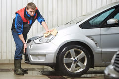Worker cleaning car with water and sponge Royalty Free Stock Photo