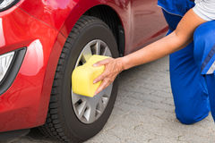 Worker Cleaning Car Wheel With Sponge. Mature male worker cleaning car wheel with sponge Royalty Free Stock Photo