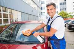 Worker Cleaning Car Windshield. Mature male worker cleaning car windshield with cloth and spray bottle Stock Image