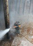 Worker cleaning column of a ship. With high pressure water Royalty Free Stock Photo