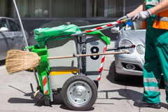 Worker of cleaning company in green uniform with garbage bin. Stock Photography