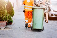 Worker of cleaning company in orange uniform. With a green garbage bin Stock Images