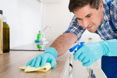 Worker Cleaning Countertop With Rag. Young Worker In Overall Cleaning Countertop With Rag In Kitchen Royalty Free Stock Images