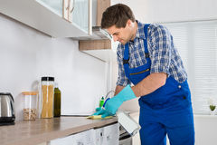 Worker Cleaning Countertop With Rag. Young Worker In Overall Cleaning Countertop With Rag In Kitchen Stock Photography