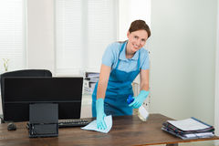 Worker Cleaning Desk With Rag. Young Happy Worker Cleaning Desk With Rag In Office Royalty Free Stock Photography