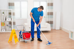Worker With Cleaning Equipments And Wet Floor Sign. Happy Worker With Cleaning Equipments And Wet Floor Sign In House Royalty Free Stock Photography