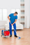 Worker With Cleaning Equipments And Wet Floor Sign. Happy Worker With Cleaning Equipments And Wet Floor Sign In House Royalty Free Stock Images