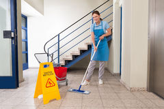Worker With Cleaning Equipments And Wet Floor Sign. Young Happy Female Worker With Cleaning Equipments And Wet Floor Sign On Floor Stock Image