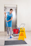 Worker With Cleaning Equipments And Wet Floor Sign. Young Happy Female Worker With Cleaning Equipments And Wet Floor Sign On Floor Royalty Free Stock Image