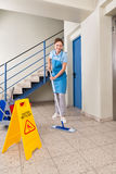 Worker With Cleaning Equipments And Wet Floor Sign. Young Happy Female Worker With Cleaning Equipments And Wet Floor Sign On Floor Stock Photo