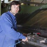 Worker cleaning fabric mashine Royalty Free Stock Photo